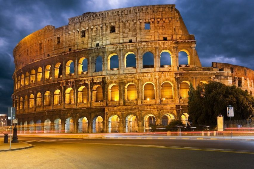 Colosseum and traffic lights at night in Rome, Italy